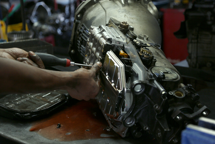 Auto shop owner taking apart his car transmission.