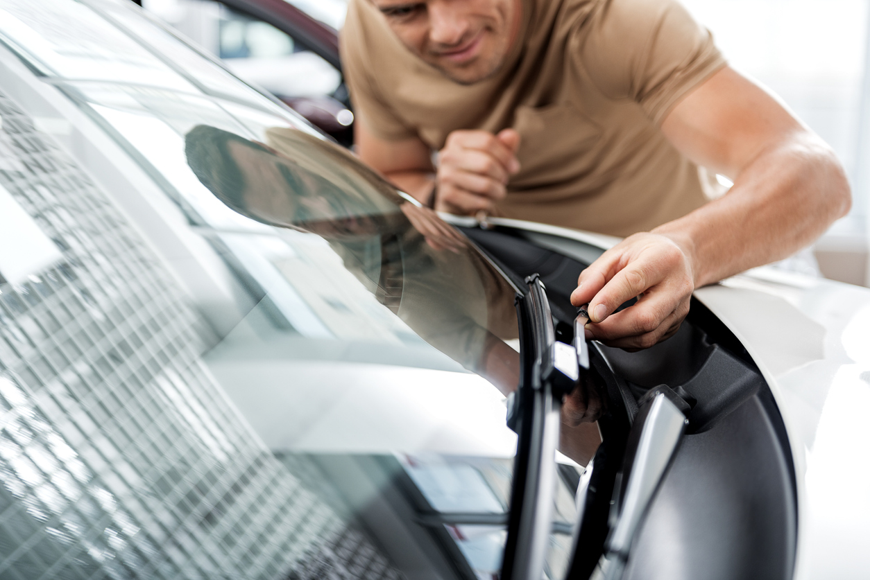 Outgoing man straightening wipers in automobile. He standing near it. Adoration concept