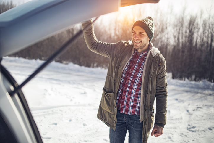 man opens car boot in snow