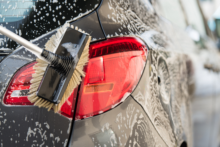 Washing a car with scrub brush.