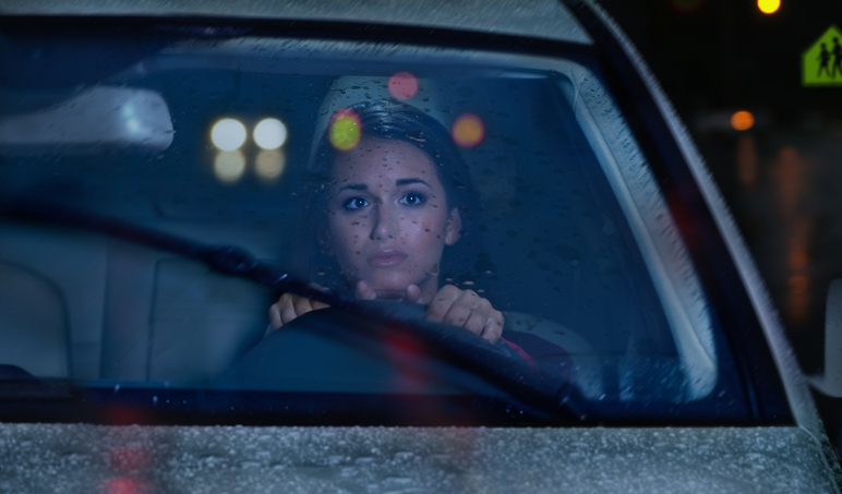 Young woman driving in rain