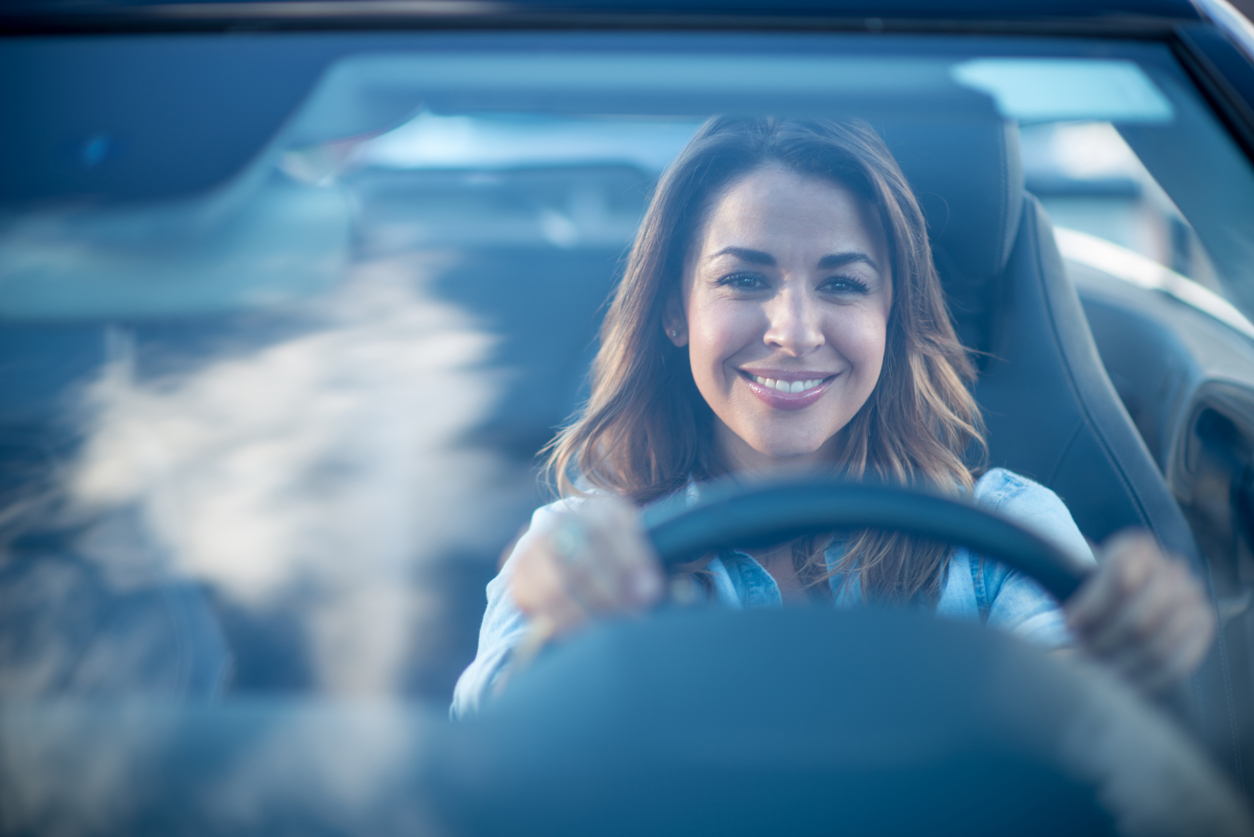 Happy woman driving a car and smiling