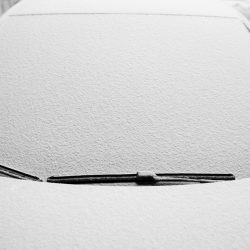 Snow-covered windshield wipers and windshield on the car.