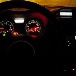 Night illuminated dashboard CLOSE-UP A black interior MOTOR VEHICLE with lighting equipment, red lines, with indicators and some measure equipment -- format 4x3 Close up on the steering wheel. ZERO