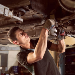 Repair man fixing and servicing car in repair station under lifted car during repair in garage