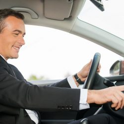 Driving with comfort. Side view of cheerful mature man in formalwear driving car and touching dashboard with finger