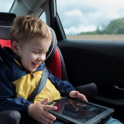 Happy little boy in the car sitting in child safety seat and playing with tablet PC