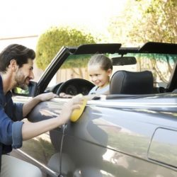 Father and daughter polishing convertible