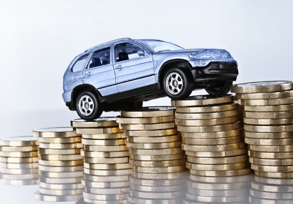 Car drives up a hill made of gold coins