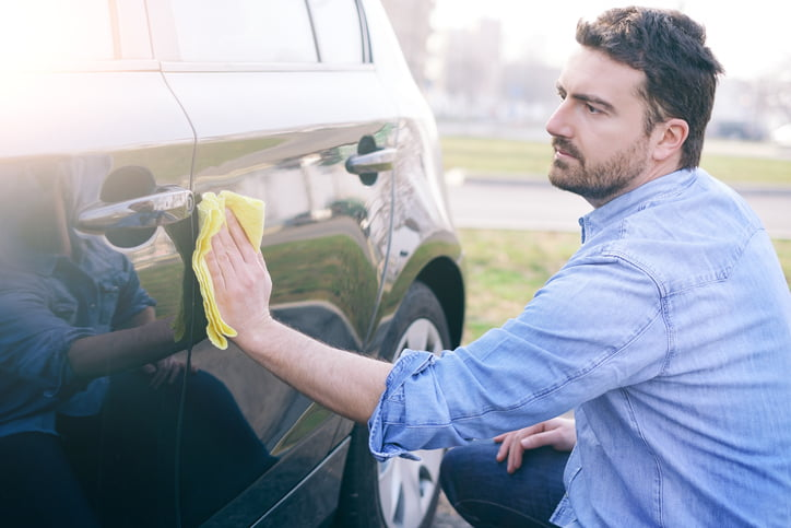 Man taking care and cleaning his new car with sponge