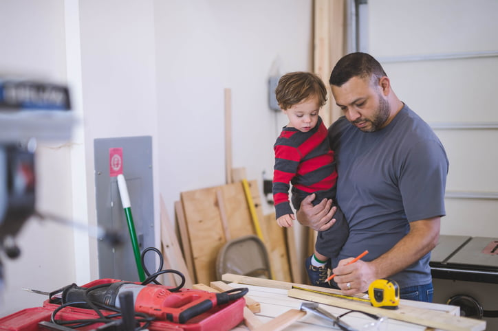 Dad and young son work construction project together in garage workshop