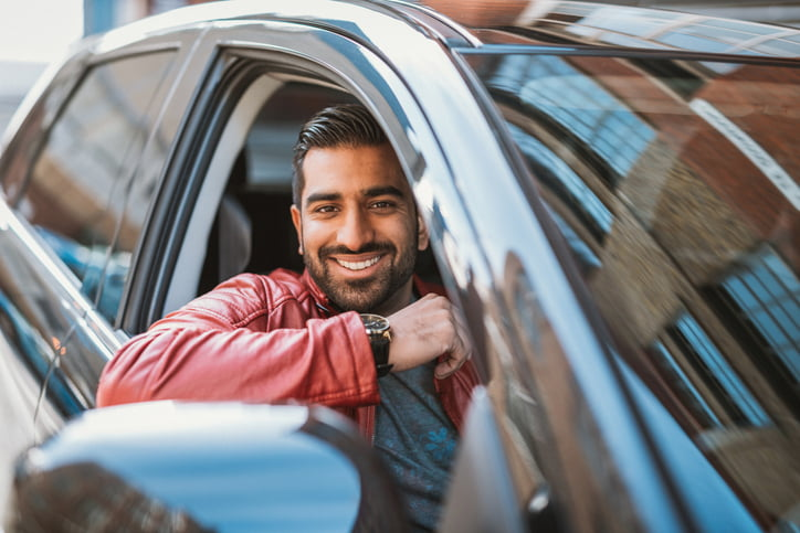 Young handsome man driving luxury car. Successful businessman driving new car to work and back home. Indian man is also using possibility of crowd-sourced taxiing to earn additional money for personal income