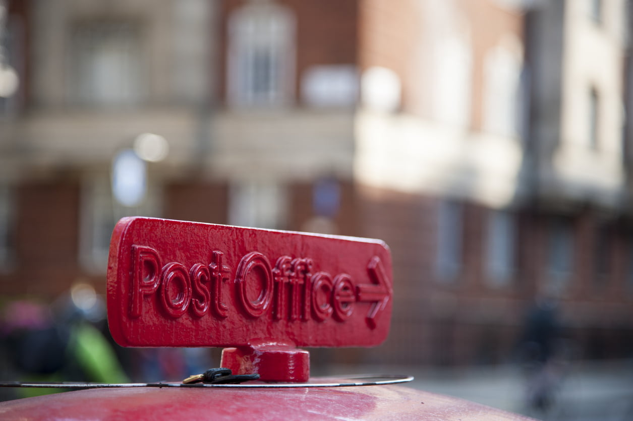 Old red cast iron sign to the Post Office in London, UK