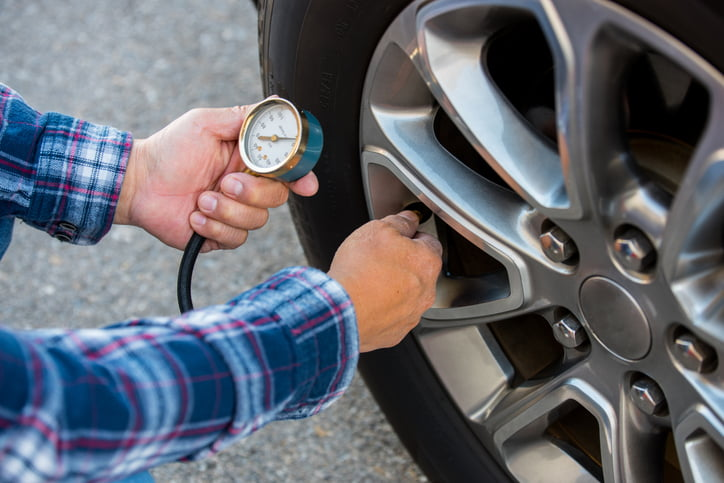 Man Checking Tyre Pressure While Maintaining Tyres