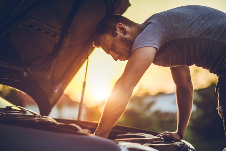 Young man repairing car on the side of the road