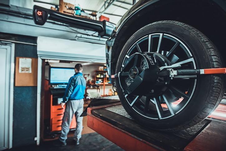 mechanic aligning car wheels