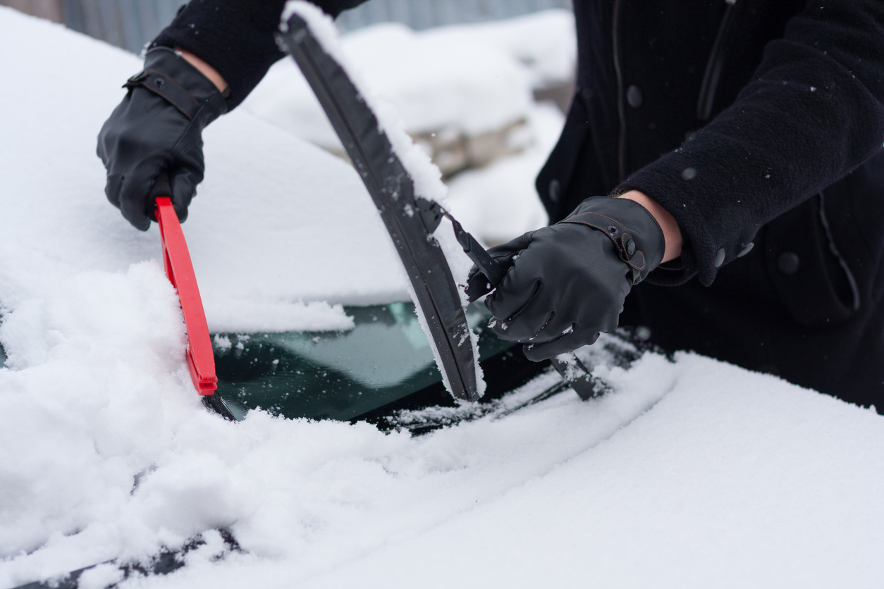 Driver clean his car after snowfall