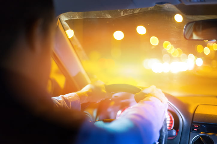Inside view of a man driving a car at night. Bright lights at background.