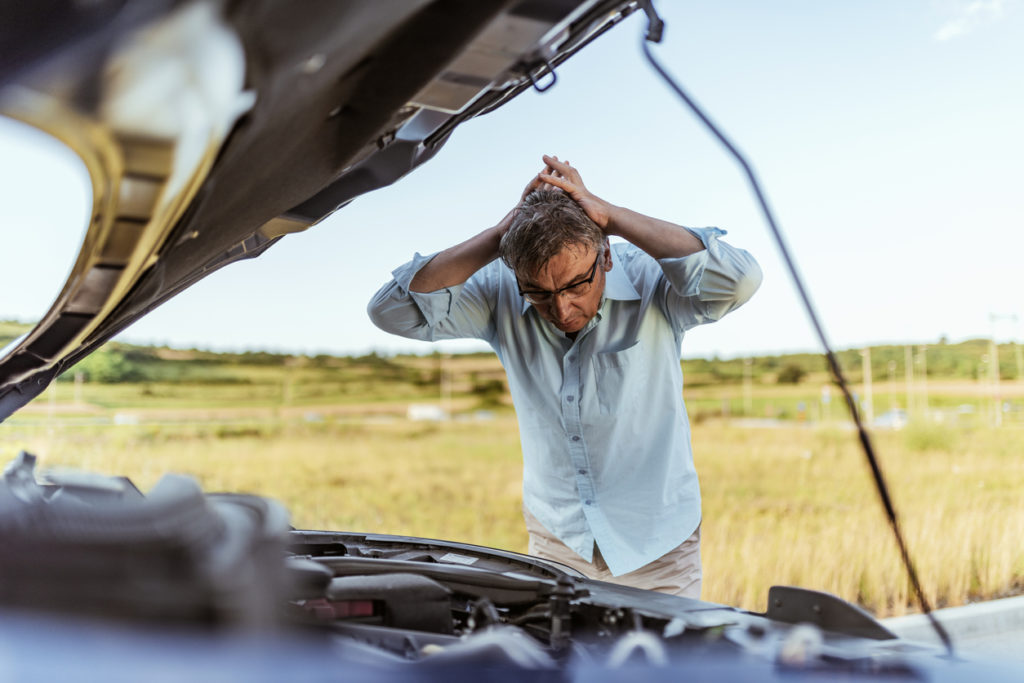 angry man looking as broken down car