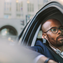 businessman listening to podcast in his car