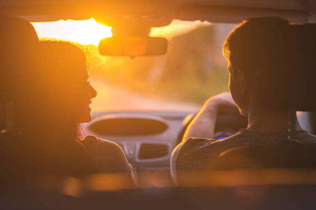 couple driving at evening sunset