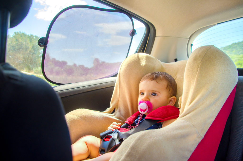 baby in baby seat in back of car