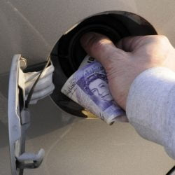 Filling up a car, money in hand