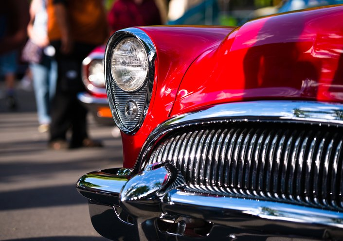Retro Vintage red car with chrome accents headlamp grille and bumper reminiscent of the outline face predatory sharks in traditional outdoor exhibition of old cars in a small American provincial town.