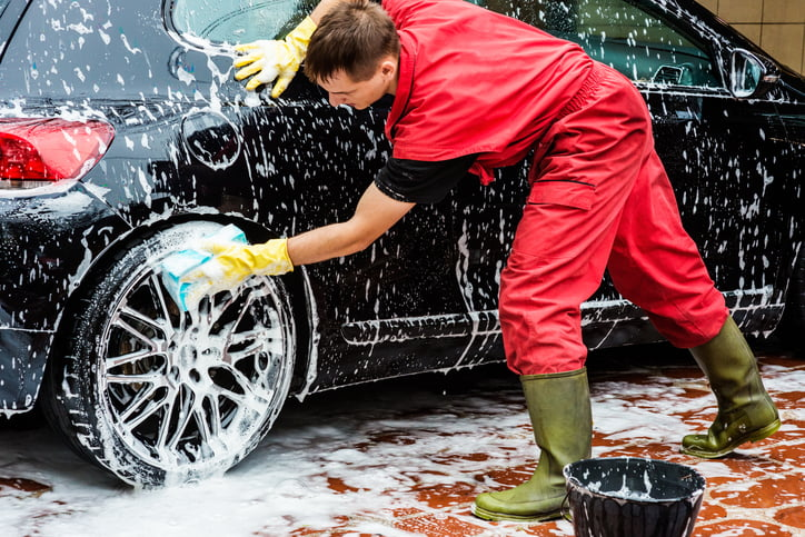 Male worker at car wash service washing the car tire.