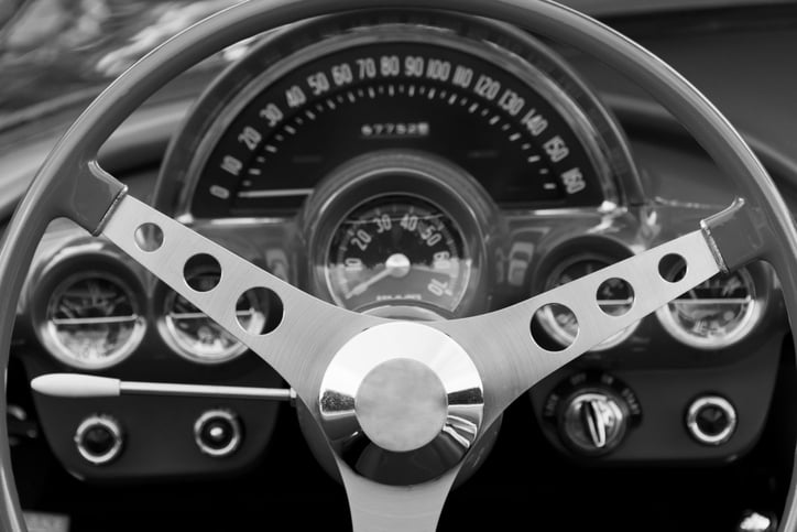 Monochrome image steering wheel and interior of a classic car.
