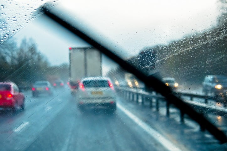 heavy rain on windscreen wipers while car drives on motorway