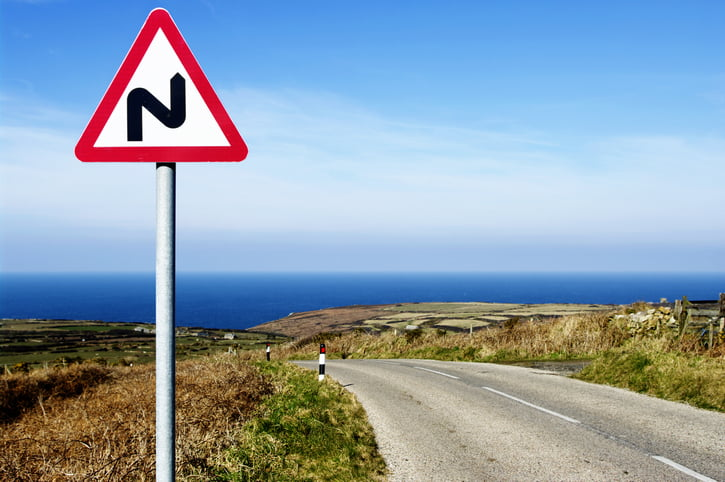 Bend warning sign on North Coast Road, Land's End, Cornwall UK. Sea and typical small costal fields in background
