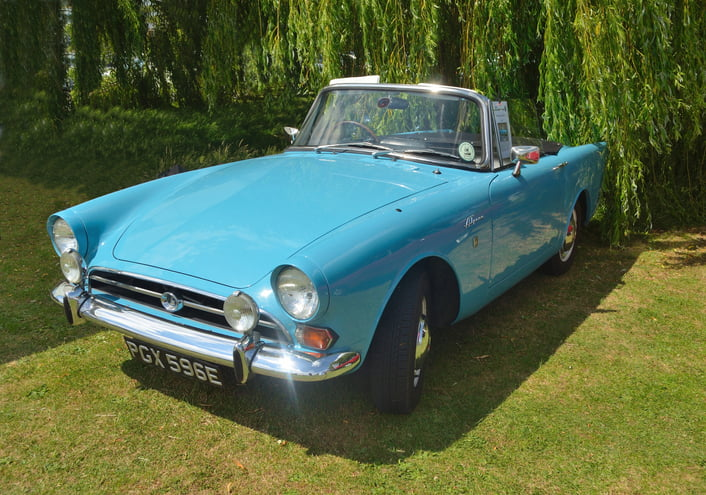 Classic Light Blue Sunbeam Alpine 2 door convertible motorcar restored and on show outside under willow trees.