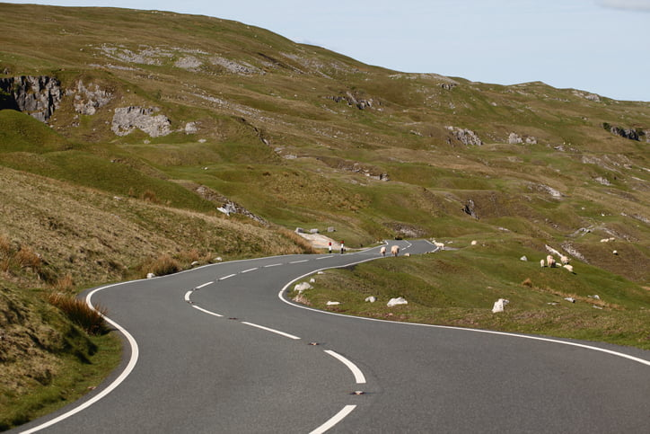 A country road in the Welsh Mountains with sheep and rugged countryside.