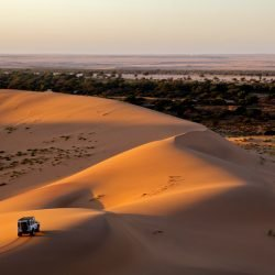 A car is driving through sand dunes