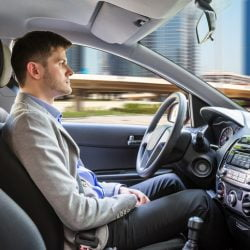 Side View Of A Young Man Sitting Inside Autonomous Car