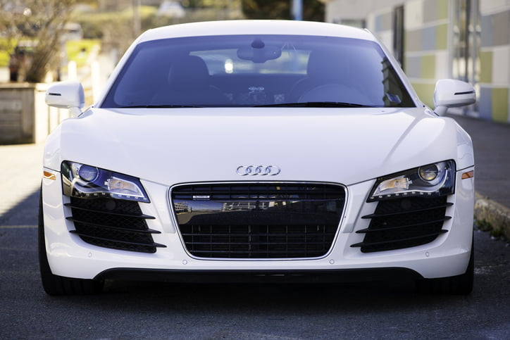 Dartmouth, Nova Scotia, Canada - October 24, 2012: An Audi R8 front view showing the Audi emblem in center of hood, and the world's first, all-LED headlights. Vehicle is parked in the shade of a building which can be seen to the right of frame. The Audi R8 is a mid-engined sports car that features a 4.2L V8 engine producing 420 HP.