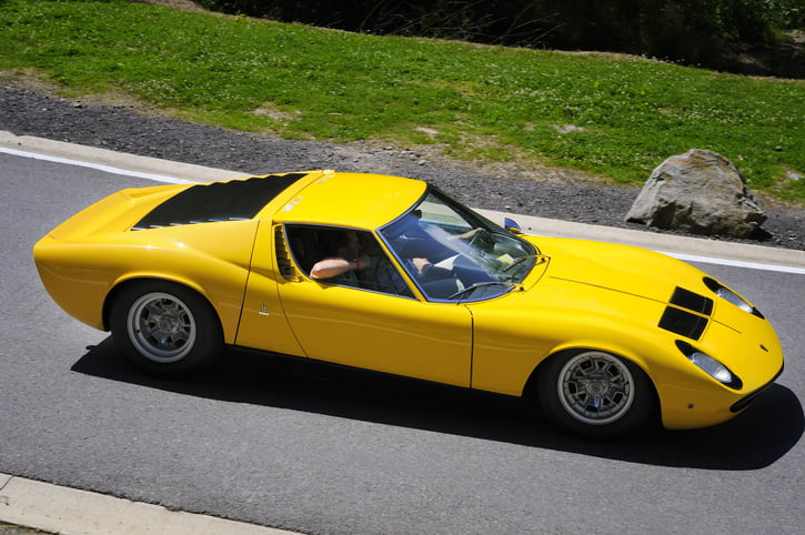 Spa, Belgium - June 29, 2008: Yellow classic Lamborghini Miura S sports car driving on a country road. Two persons are sitting in the car.