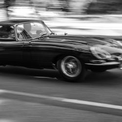 Jaguar E-Type driving at high speed on a road through a forest