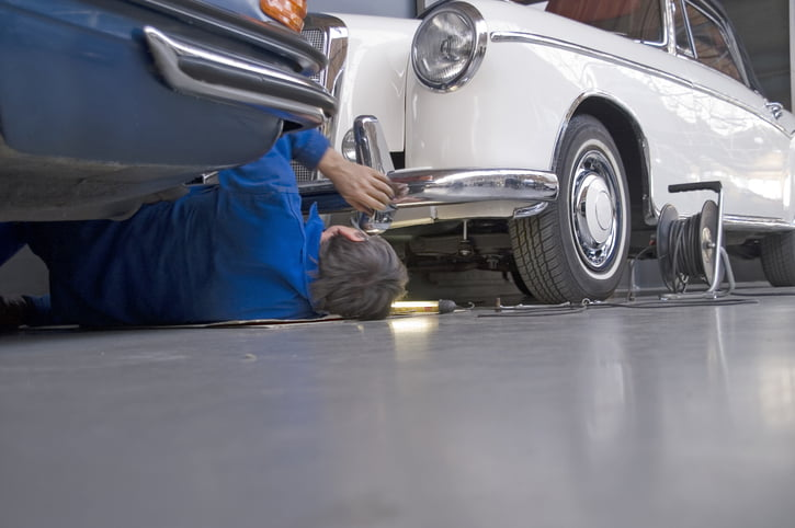 Car mechanic lies between two old timer cars.