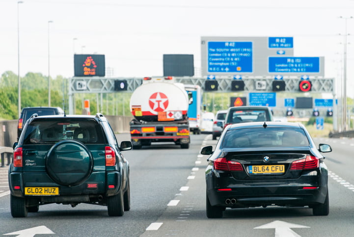 M42 Motorway, UK - Rear view of busy traffic, with a group of signs in the background on the M42 motorway in the English Midlands.