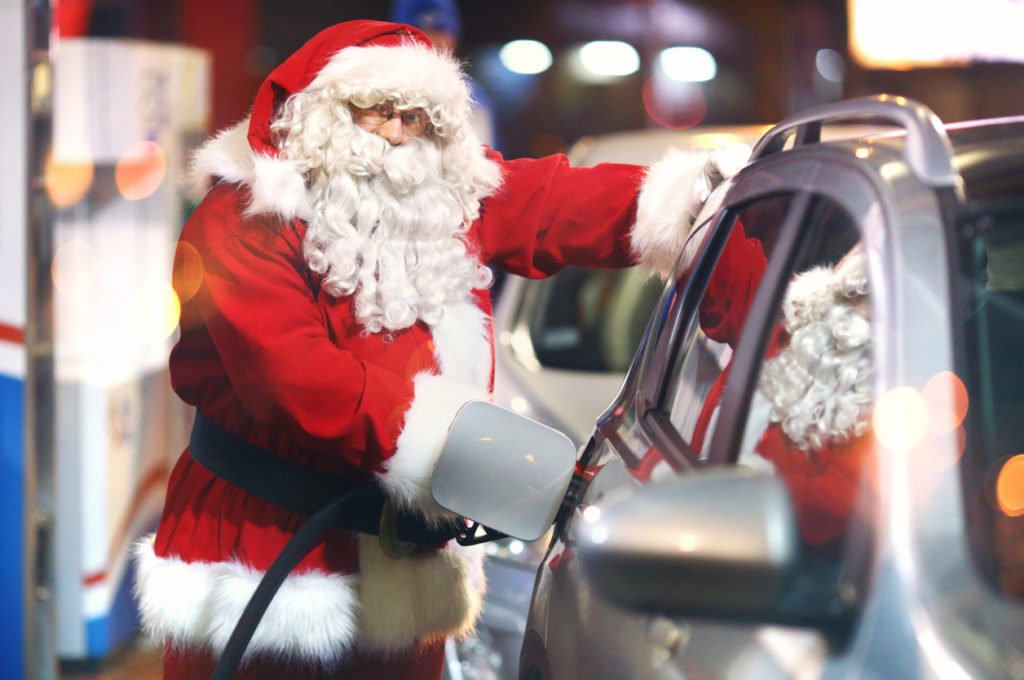 Santa Claus putting petrol in his car