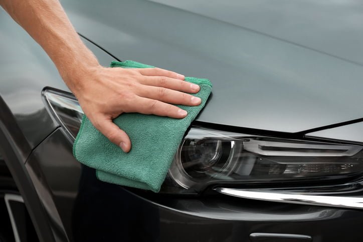 Man washing car headlight with rag, closeup