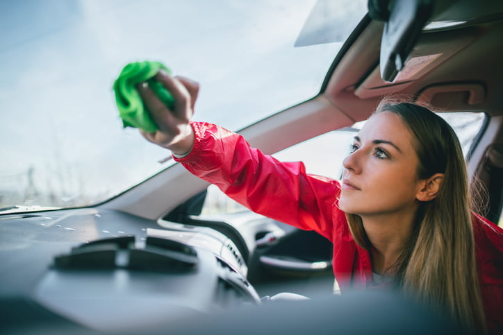 Young woman washing car and cleaning car windows