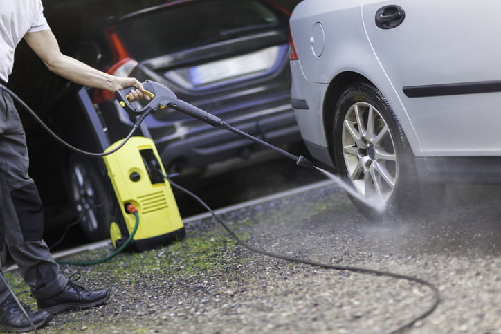 A person cleaning the car by a garage with a high pressure washer.