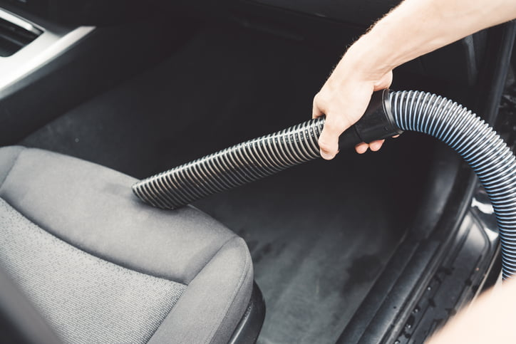 Man is vacuuming the indoors of his car