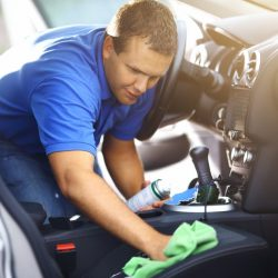 Adult caucasian man cleaning passenger seat with a green cloth and cleaning product. He applied some cleaning foam onto the seat. The guy has short brown hair and wearing blue polo shirt