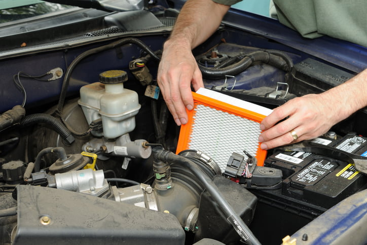 Man replacing an automotive air filter.