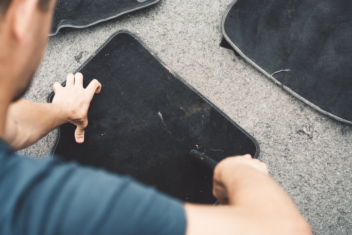 Man is exhaustively cleaning car mats outdoors