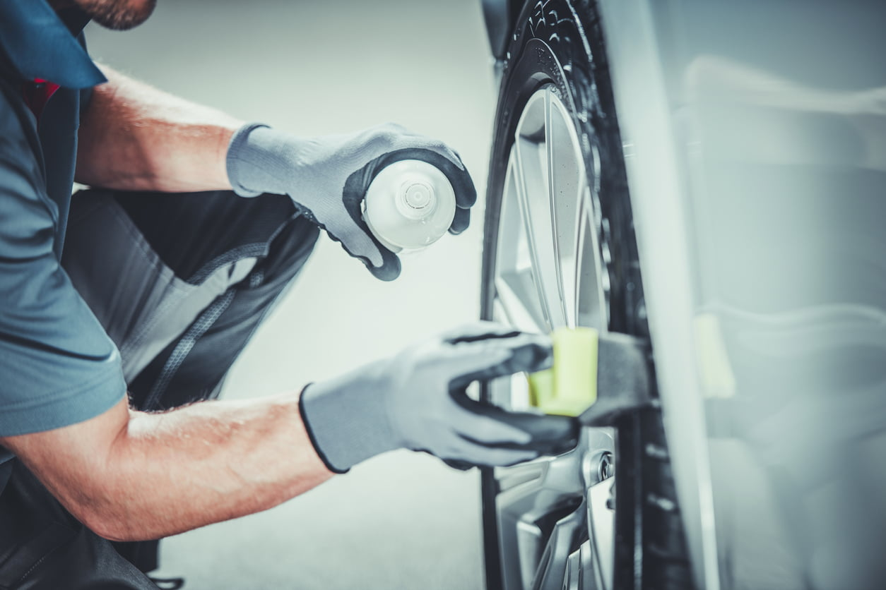 Man cleaning car wheels with spray